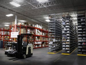 A large warehouse with three tall gray shelves and two tall red shelves that hold lots of cardboard boxes