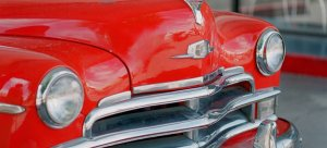 The front bumper of a bright red vintage car with two headlights and a silver bumper