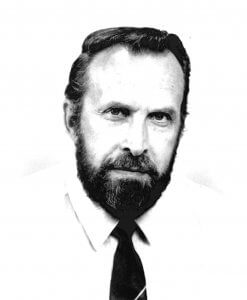 A closeup of a bearded Don Craighead wearing a white shirt and dark solid colored tie