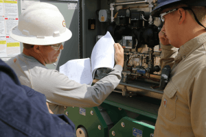 Two men wearing khaki Carhartt shirts, safety glasses, and construction helmets while viewing blueprint plans outside