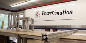 A large white sign on a white wall that says Power/mation on it with a large table that has metal enclosure boxes resting on top of it