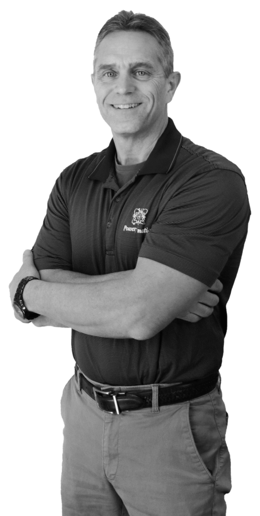 A black and white image of Jeff Johnson from the waist up crossing his arms while smiling and wearing a striped Power/mation polo shirt