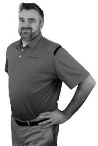 A black and white image of Lance Waffensmith from the waist up with his hands on his hips wearing khakis and a Power/mation polo