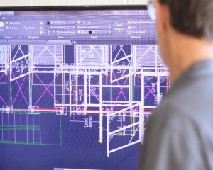 A male engineer is viewing a wireframe of a custom fencing project on a large monitor