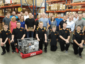 A large group of Power/mation employees posing for a photo with six young boys in black, yellow, and orange polos next to a robotic machine with the number 2062 on it